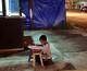 Dječak beskućnik piše zadaću i uči ispod svjetla Mcdonald'sa